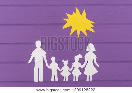 The silhouettes cut out of paper of man and woman with two girls and boy under the sun on purple wooden background. Concept of family unity