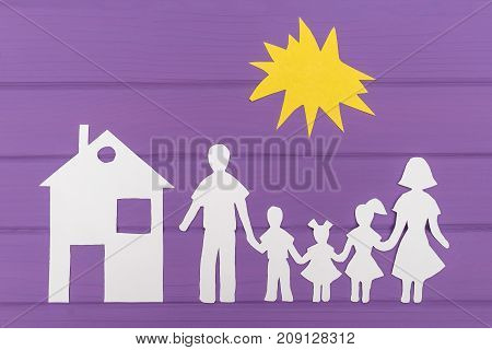 The silhouettes cut out of paper of man and woman with two girls and boy under the sun, house near on purple wooden background. Concept of family social protection