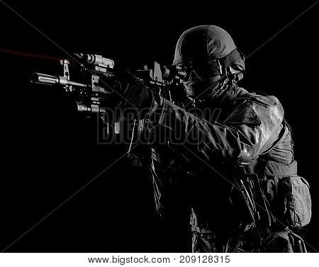 American Soldier In Combat Ammunition With A Weapon Equipped With Laser Sights Aims At The Target