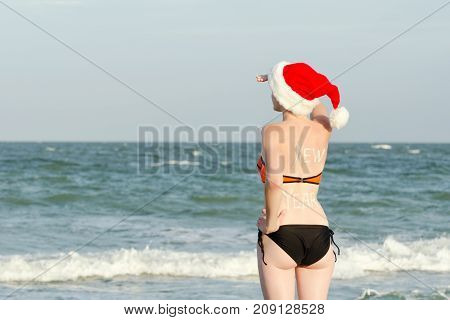 Girl In Santa Hats With The Inscription New Year On The Back Looks Into The Distance. Sea Shore.