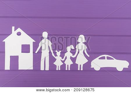 The silhouettes cut out of paper of man and woman with two girls, house and car near on purple wooden background. Concept of family protection