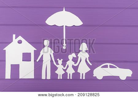 The silhouettes cut out of paper of man and woman with two girls under the umbrella, house and car near on purple wooden background. Concept of family protection