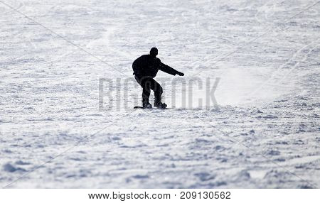 Snowboarding man at flattened piste - slope . In the park in nature