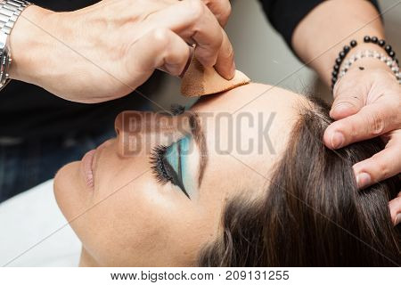 Makeup Artist Applying Foundation Using A Sponge To A White Woman