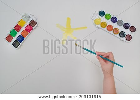 Child hand with brush drawing yellow sun on white paper. Child drawing top view
