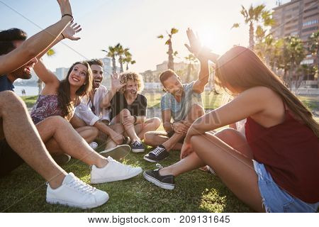 Group Of Friends Sitting Outside Giving High Five