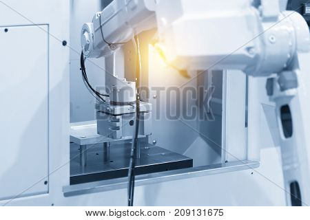 The robot in modern CNC machine operation.The modern CNC manufacturing process using autonomous robot for setting work piece.