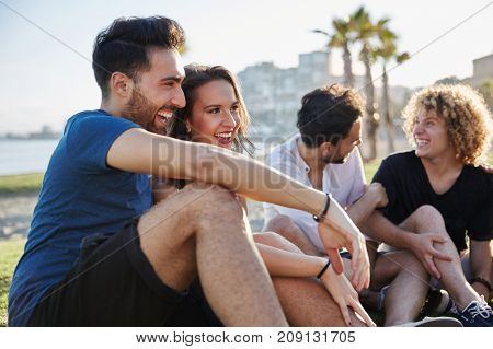 Portrait of happy couple sitting with friends outside talking