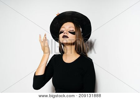 beautiful witch is going to a Halloween party. A girl in a witch hat with leaves. Autumn holiday Halloween. Halloween style