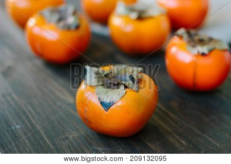 Fresh orange persimmons upside on wooden table
