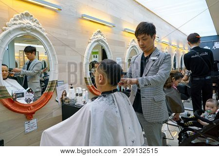 BUSAN, SOUTH KOREA - MAY 28, 2017: hair stylist at work in hairdresser salon at Lotte Department Store.