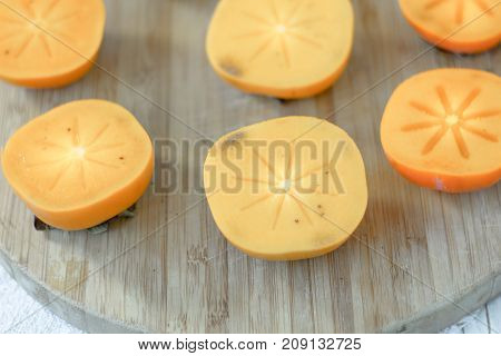 Halves of persimmon fruit on brown wooden background