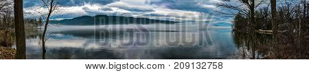 Panoramic view of a moody lake with clouds