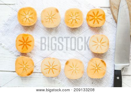Pieces of persimmon fruit frame on white background