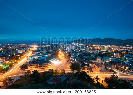 Gori, Shida Kartli Region, Georgia. Gori Cityscape In Evening Illumination Under Blue Sky In Twilight. Cathedral Of The Blessed Virgin Mary In Night Illuminations Lights. Travel Destination