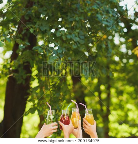 Group of people do cheers with detox juice cocktails on green nature background witn free space. Diet on the go, well being and weight loss, celebration, health, vegetarian food concept