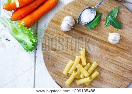 Top view of dry rigatoni pasta and some vegetables over wooden board