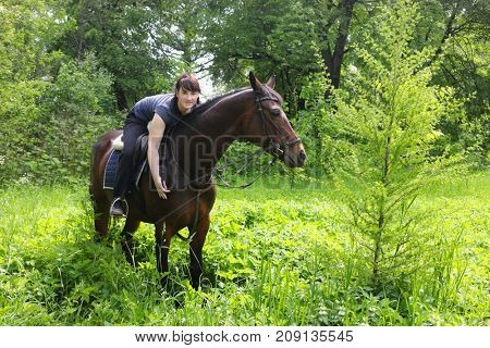 Pretty happy girl sits on horse among trees in green summer forest