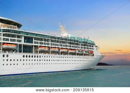 Luxury cruise ship sailing to port on sunrise