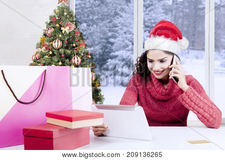 Beautiful woman purchasing Christmas presents online with a digital tablet computer while wearing a Santa hat and make a phone call at home