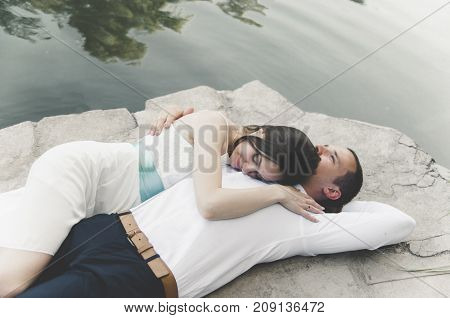romantic couple in wedding clothes lay embracing on a stone near the river