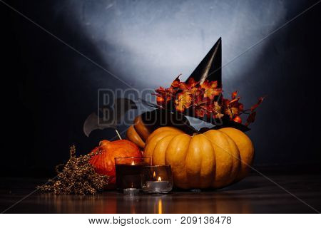 autumn holiday, a large pumpkin, golden leaves on a black witch hat,candles, dry grass.Halloween, a mesmerizing picture