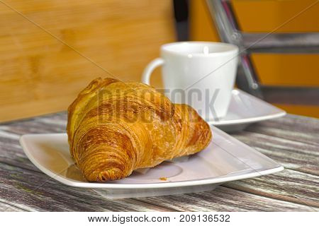 Traditional French butcher croissant on a plate. Cup of coffee in the background.