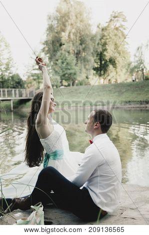 happy newlyweds rest near lake in park