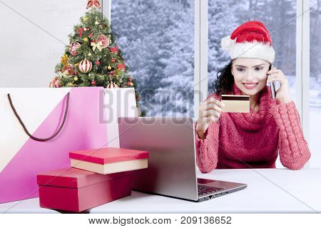 Happy woman buying Christmas gifts online with a credit card and laptop computer while making a phone call and wearing a Santa hat at home