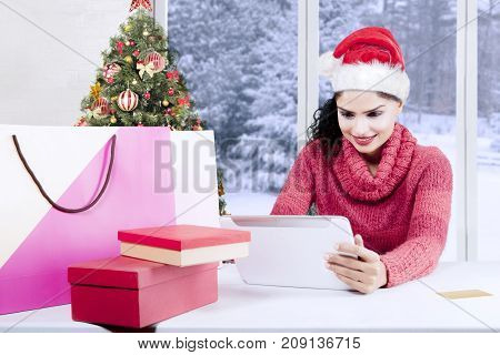 Beautiful woman wearing a Santa hat and buying Christmas gifts online with a digital tablet computer at home