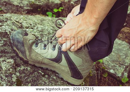 Boy getting a shoe leaning against a rock