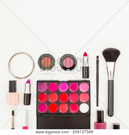 Feminine desk with cosmetics - lipstick, nail polish and accessories on white background. Flat lay, top view.
