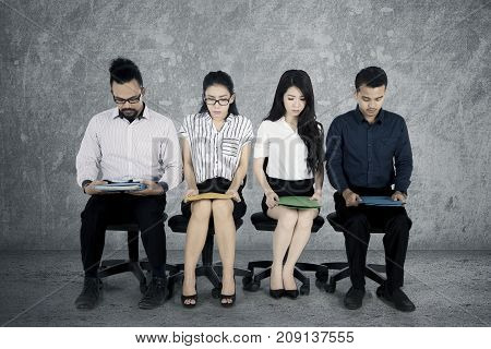 Group of multiracial workers sitting on the office chair and looks strained while waiting for a job interview