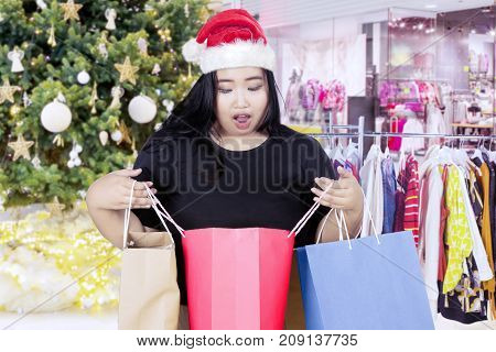Image of fat woman looks shocked while opening a shopping bag and standing near Christmas tree in the mall