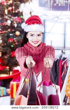 Pretty young woman wearing a Santa hat and giving shopping bags in the mall or shopping center