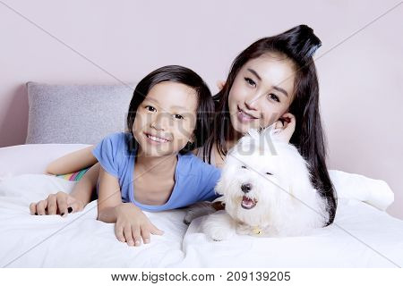 Happy little girl lying on the bedroom with her mother and Maltese puppy at home