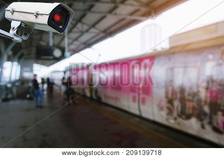 CCTV security camera system operating with blurred image of sky train at train station transportation surveillance security and safety technology concept