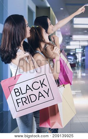 Three happy teenage girls pointing at copyspace while holding shopping bags in the mall or shopping center
