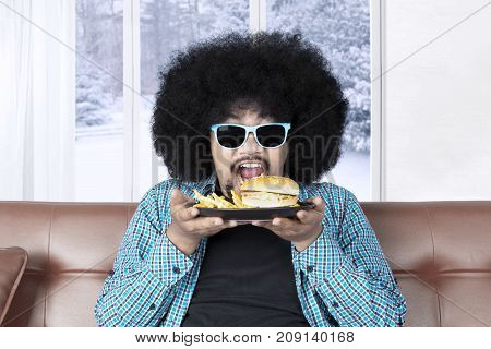 Funny Afro man with curly hair sitting on the sofa while wearing sun glasses and eating a plate of cheeseburger with french fries