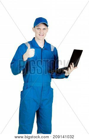 European male mechanic standing in the studio while showing thumb up and holding a laptop