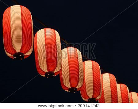 Paper red-white japanese lanterns Chochin hanging shines on dark nigrt sky background.