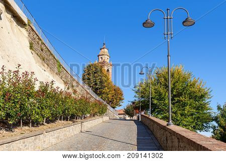 Narrow street leading towards belfry along lampposts and autumnal trees under blue sky in small town of Diano d'Alba in Piedmont, Northern Italy.