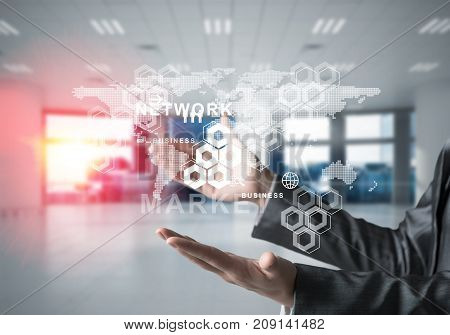 Business woman in suit with media interface and interactive world map in her hands. Sunlight and office view on background. Mixed media.