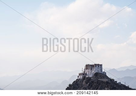 Stakna Gompa on the top of mountain with blue and cloudy sky background