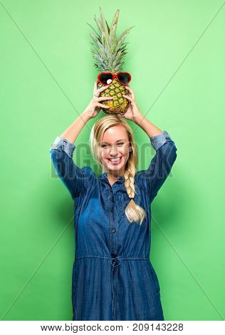 Happy young woman holding a pineapple on a green background