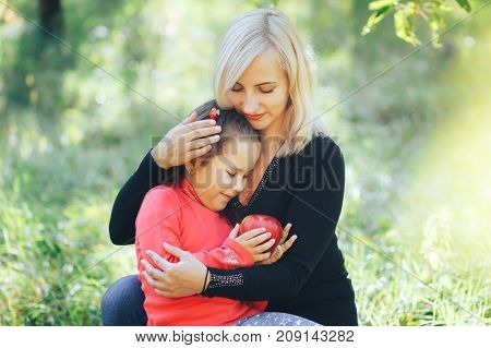 The blonde mother hugged her daughter and treated him with an apple
