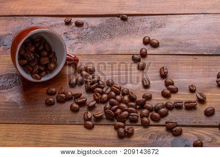 scattering of beans and a cup om broun wooden background
