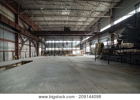 A large empty factory building. Above it hangs a cargo hook on chains.