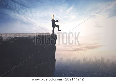 Blindfolded businessman with cardboard head finding a way and walks on the cliff with a city background