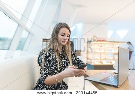 A stylish woman sitting on a couch in a stylish light cafe and writing a message on a swarthy. There is a laptop and a coffee on the table. Freelancer working in coffee shop.